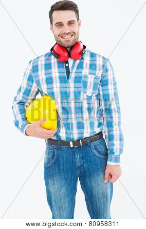 Portrait of confident manual worker with hardhat and ear muffs on white background