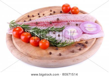 Pangasius fillet on wooden cutting board with cherry tomatoes and spices isolated on white poster