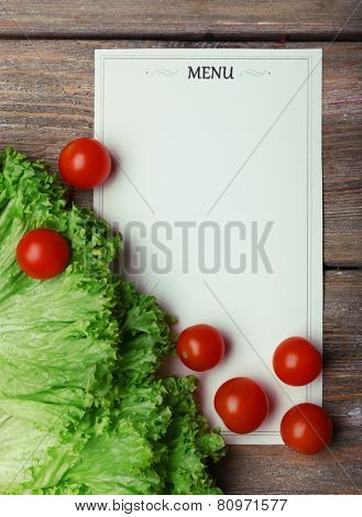 Menu sheet of paper with cherry tomatoes and lettuce on rustic wooden surface background