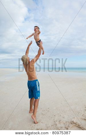 Father and son enjoy summer day at tropical beach.