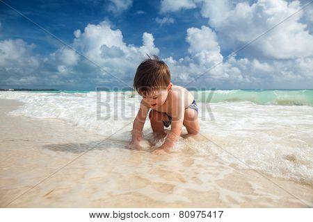 Little boy enjoys summer day at the tropical beach.