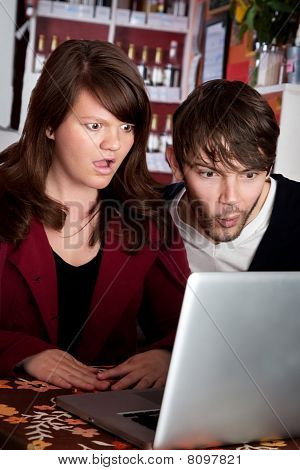 Woman and man staring with shock at laptop computer poster