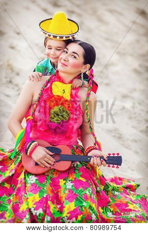 Toned photo of little boy hugging his mother in Mexican costume and playing the guitar