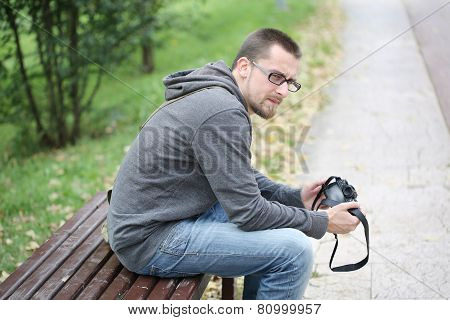 Young Man Sitting On A Bench With Photo Camera