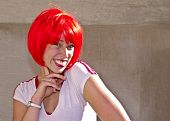 Smiling redhead young woman posing outdoors. poster