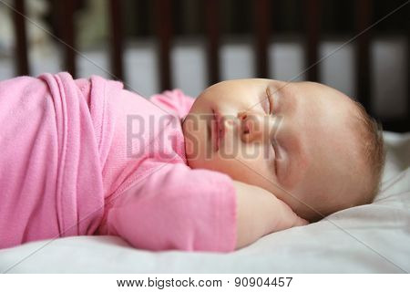 Sweet Newborn Baby Girl Asleep In Crib