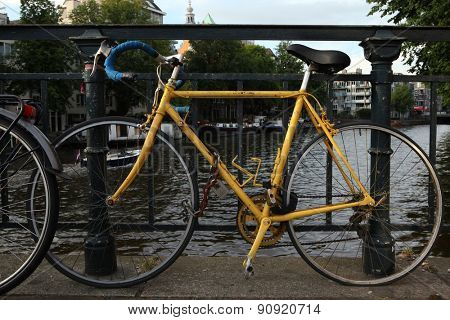 AMSTERDAM, NETHERLANDS - AUGUST 9, 2012: Old yellow bicycle parked on the bridge over a gracht in Amsterdam, Netherlands.