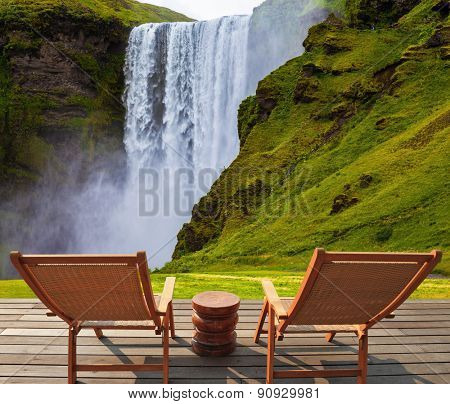 Magnificent famous waterfall Sk���³gafoss, Iceland. A powerful jet Sk���³gar river falls from  large glacier. On stony ground in front of the waterfall are two wooden deck chairs