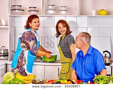family of three people cooking at kitchen. Grandfather and grandmother with his adult daughte