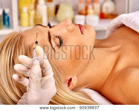 Beauty woman giving botox injections on forehead.