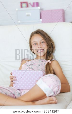 Preteen school girl of 8-9 years old posing with ipad tablet pc, looking at camera and smiling in home room