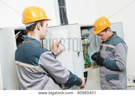 electrician builder engineer workers with electric cable wiring of fuse switch box poster