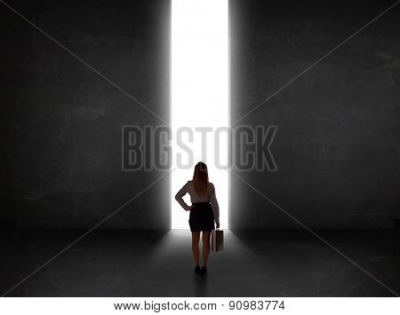 Business person looking at wall with light tunnel opening concept