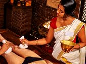 Young woman having indian feet Ayurveda spa massage. poster