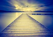 Vintage photo of beautiful sunset over calm lake. Landscape photogrpahed in Mazury lake district. poster