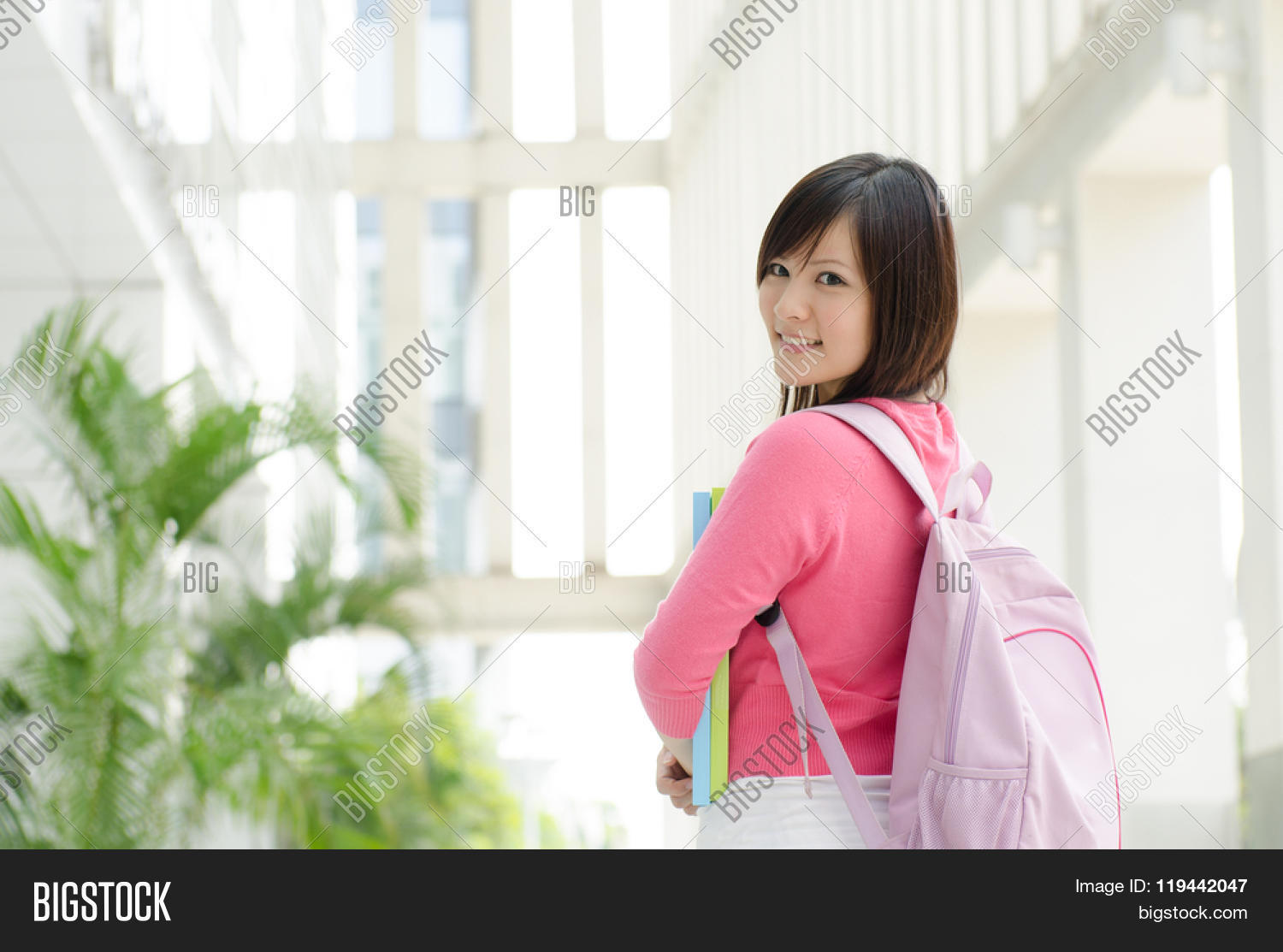 Young Asian Teen Student Standing Outside School Campus Building Holding File Folder And Smiling