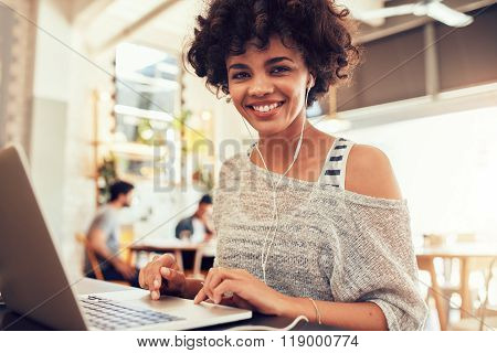 Happy Young African Woman  At Cafe With A Laptop