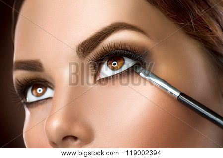 Makeup. Woman Make-up Applying closeup. Eyeliner. Cosmetic Eyeshadows. Eyeline brush for Make up. Beauty Girl with Perfect Skin. Eyelashes. Brown eyes. Makeover