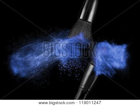 makeup brush with blue powder isolated on black