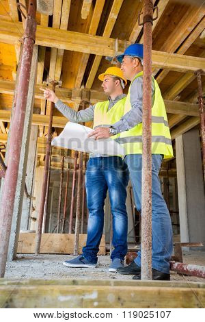 Supervisor of the construction site with architect looking building up on construction site