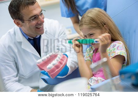 Young cute girl hold big tooth brush and make joke with dentist