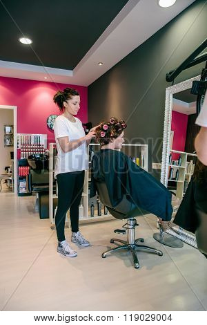 Hairdresser curling woman hair in a beauty salon