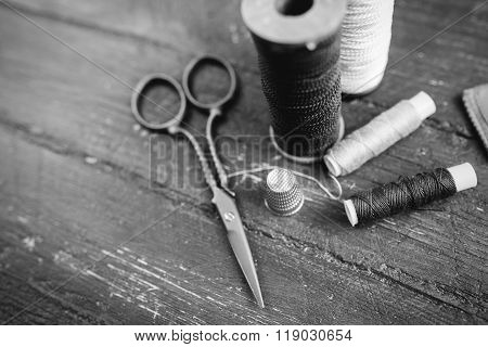 Sewing accessories: bobbins of thread, scissors, needle, thimble on wooden table. Black and white ph