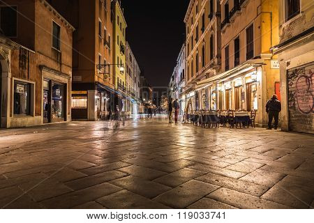 VENICE ITALY - 13TH MARCH 2015: Strada Nuova in Venice at night showing shops restaurants and the blur of people walking