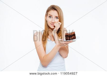 Doubtful pretty young woman on diet thinking and holding piece of cake over white background