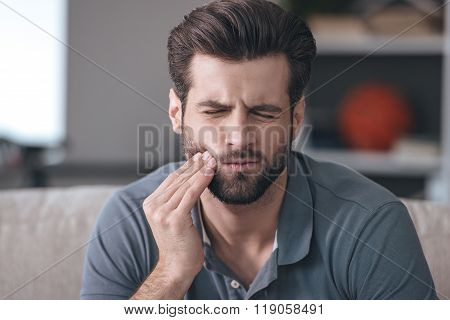 Toothache. Frustrated young man touching his cheek and keeping eyes closed while sitting on the couch at home
