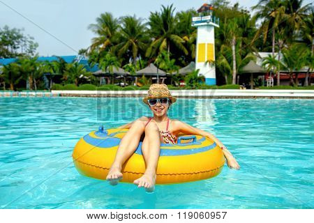 Tween girl relaxing on the inflatable ring in the water park in Thailand