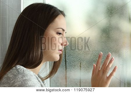 Sad Woman Looking Rain Through A Window