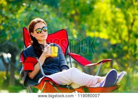 Beautiful woman resting outdoors, sitting on the chair and drinking tea, spending spring vacation in the camp, enjoying calm and peaceful holidays