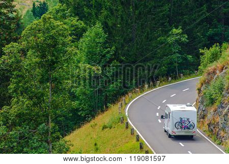 Camper Journey. Small Class B Camper Van with Whole Family Bikes on the Forest Road. Camper Travel Theme. poster