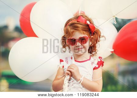 Little Curly  Girl Holding Red And White Ballons Outside