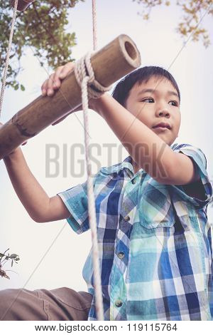 Asian Boy Climbing On Rope Ladder Made Of Wood.travel And Adventure Concept. Retro Style.