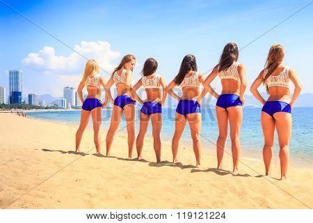 Cheerleaders Stand Backside Hands On Hips On Beach Against Sea