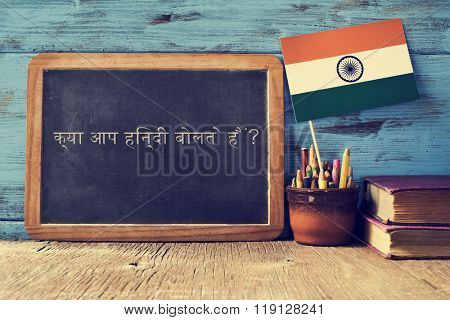 a chalkboard with the question do you speak hindi? written in hindi, a pot with pencils, some books and the flag of India, on a wooden desk