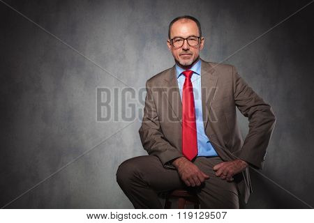 mature handsome businessman wearing suit and glasses posing seated while looking at the camera in studio background