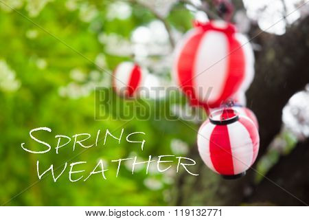 Blurred background of green tree and leaves and red and white striped lanterns at windy rainy day with white text letters