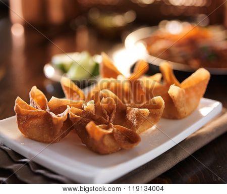 crispy fried crab Rangoon appetizer on a plate.