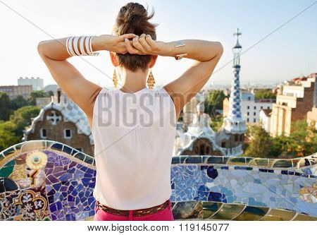Refreshing promenade in unique Park Guell style in Barcelona Spain. Seen from behind relaxed young woman tourist sightseeing in Park Guell Barcelona Spain poster