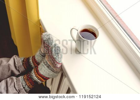 Warming By The Radiator And Drinking Hot Tea