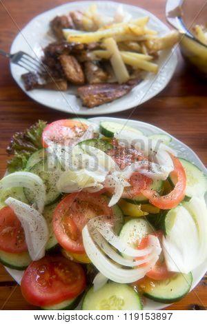 Fried potatoes, salad and fish - hake