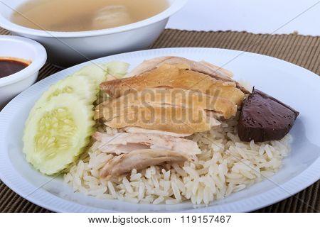 Hainanese chicken rice, steamed chicken, chicken blood and white rice on brown cloth background.