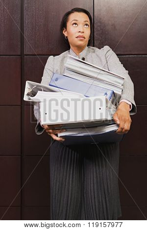 Businesswoman struggling with heavy files poster