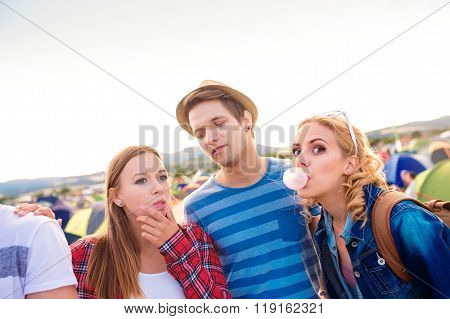 Teenagers at summer music festival blowing buble gums