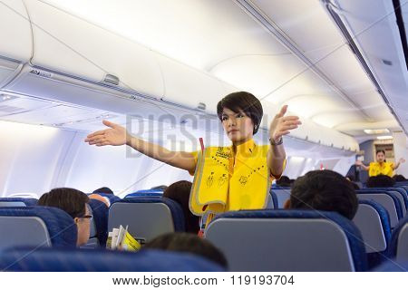 BANGKOK, THAILAND, JANUARY 05, 2016 : An air hostess of the Nok Air company is showing security rules before taking off from the Don Muang airport in Bangkok, Thailand