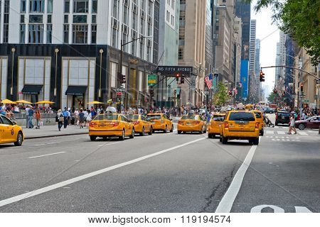 NEW YORK - CIRCA SEPTEMBER 2015: Group of iconic yellow taxi cabs driving away from the camera on 5th Ave, New York past pedestrians and commercial shops
