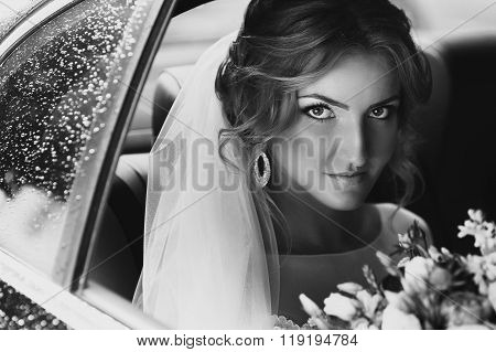 Beautiful Blonde Bride Posing In Wedding Car On Rainy Day B&w